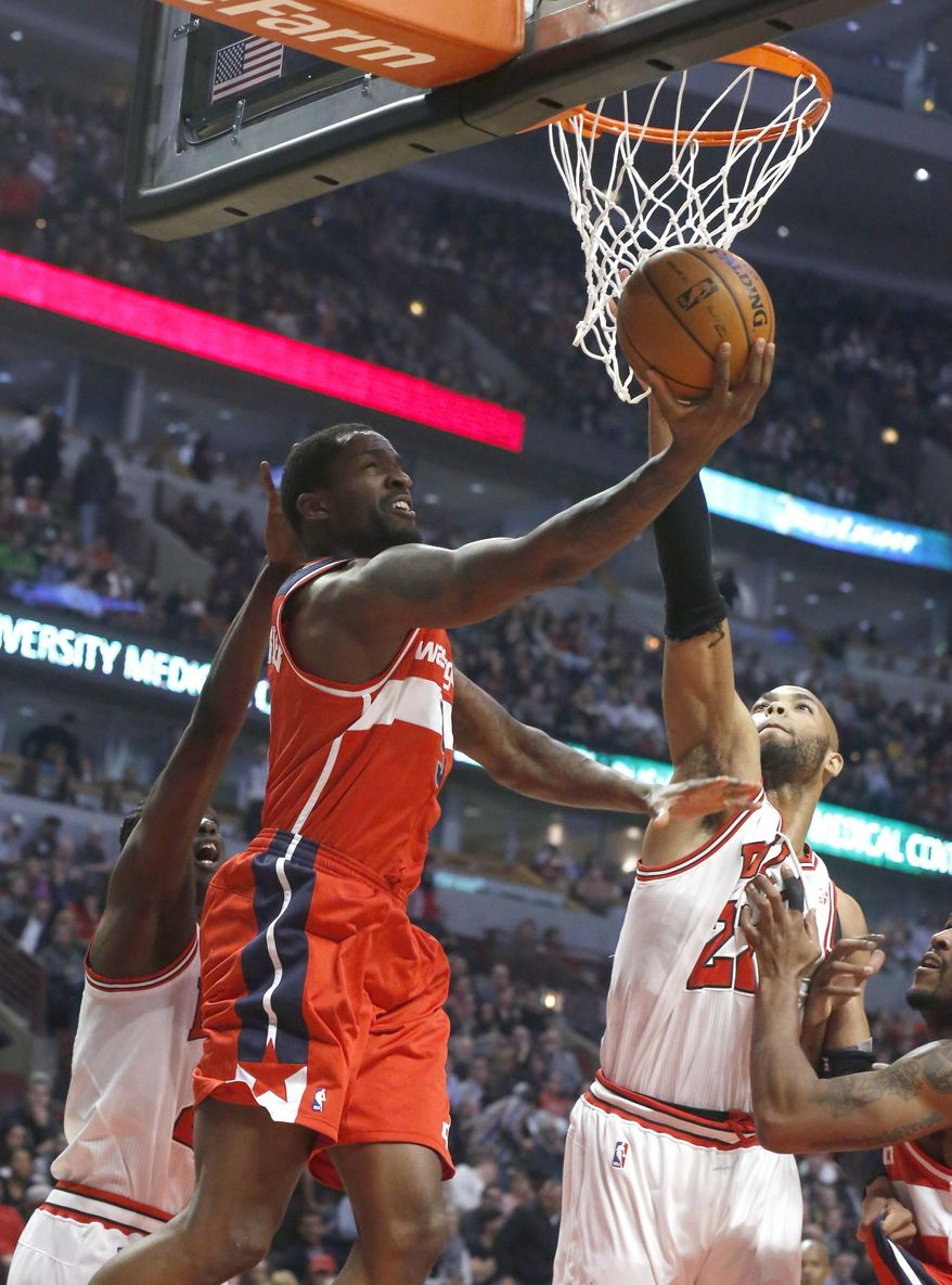 Washington Wizards small forward Martell Webster, center, scores on a reverse lay up past Chicago Bulls small forward Tony Snell, left, and Taj Gibson during the first half of an NBA basketball game, Monday, Jan. 13, 2014, in Chicago. (AP Photo/Charles Rex Arbogast)