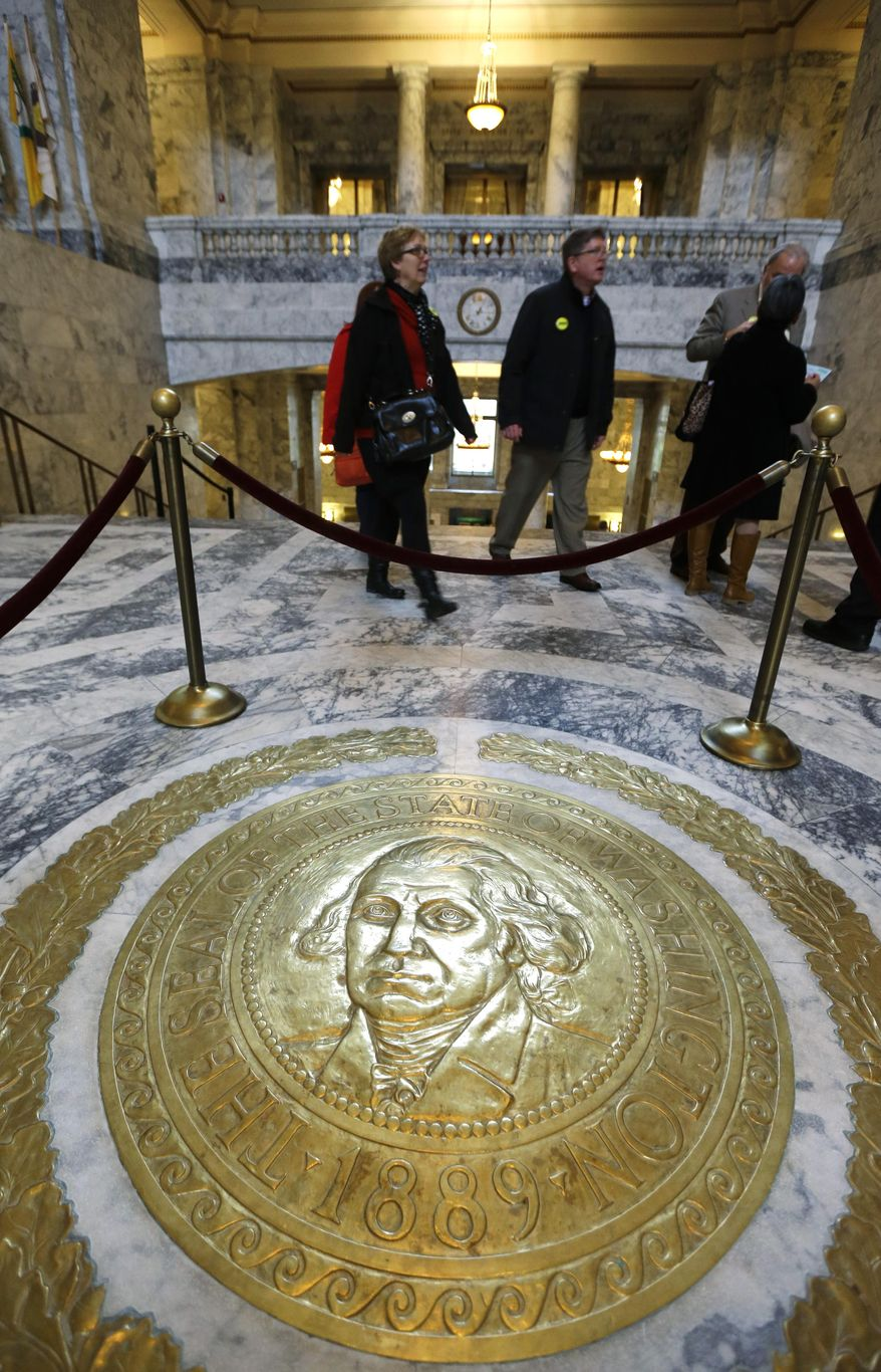 People walk past the state seal of Washington on the floor of the Capitol rotunda on the first day of the 2014 session of the Washington state Legislature, Monday, Jan. 13, 2014, at the Capitol in Olympia, Wash. (AP Photo/Ted S. Warren)