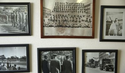 In this Jan. 3, 2014 photo, a grouping of photos from Steve Mihelsic's Illinois Army National Guard unit hang on the wall at his shop in Springfield, Ill. Six men that Mihelsic served with in the Guard in 1960s are still coming to him for their haircuts more than 52 years later. (AP Photo/The State Journal-Register, Rich Saal)
