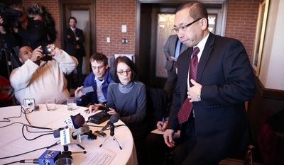 Cranston Rhode Island Mayor Allan Fung, right, takes his seat after briefly stepping out of the room while speaking with reporters during a news conference at the Chapel Grill in Cranston, Monday, Jan. 13, 2014. Fung, a leading Republican candidate for Rhode Island governor disclosed on Monday that he was responsible for a crash that killed a man 25 years ago. (AP Photo/Michael Dwyer)