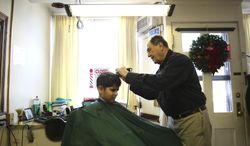 In this Jan. 3, 2014 photo, barber Steve Mihelsic cuts Michael Silas' hair in his shop in Springfield, Ill. His other customers include six men he served with in the Illinois Army National Guard in the early 1960s and they've been coming to Mihelsic for their haircuts ever since. (AP Photo/The State Journal-Register, Rich Saal)