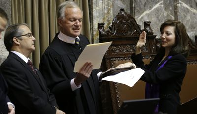Lt. Gov. Brad Owen, left, looks on as Sen. Sharon Brown, R-Kennewick, right, is sworn in as vice president pro tem of the Senate by Washington state Supreme Court Justice James Johnson, center, on the first day of the 2014 session of the Washington state Legislature, Monday, Jan. 13, 2014, at the Capitol in Olympia, Wash. (AP Photo/Ted S. Warren)