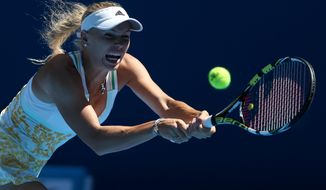 Caroline Wozniacki of Denmark makes a backhand return to  Lourdes Dominguez Lino of Spain during their first round match at the Australian Open tennis championship in Melbourne, Australia, Tuesday, Jan. 14, 2014.(AP Photo/Rick Rycroft)