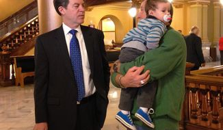 Kansas Gov. Sam Brownback, left, converses with the Rev. Dan Nicholson, right, pastor at the Lawrence Christian Center, as he holds his 19-month-old son, Aaron, before a prayer service, Monday, Jan. 13, 2014, at the Statehouse in Topeka, Kan. Brownback is wary of a proposal being developed by the Kansas Hospital Association on expanding the state's Medicaid program. (AP Photo/John Hanna)