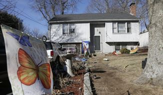A banner with the likeness of butterflies is attached to a stake in front of a home Monday, Jan. 13, 2014, in Franklin, Mass., where authorities say a brother and sister under age 10 have died after apparently getting trapped inside a hope chest. Police responded to the Franklin home at about 8 p.m. Sunday after other family members found the children together inside the chest that could only be opened from the outside. (AP Photo/Steven Senne)