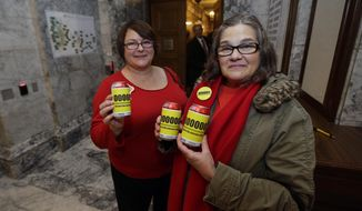 """Linda Peterson, right, a teacher at Battle Ground Middle School in Battle Ground, Wash., and Lynn Davidson, of the Washington Education Association, pose for a photo on the first day of the 2014 session of the Washington state Legislature, Monday, Jan. 13, 2014, at the Capitol in Olympia, Wash. They are holding cans of cola soda they hoped to hand out to legislators to lobby for the passage of a cost-of-living salary adjustment for teachers this year, also known as a """"COLA."""" (AP Photo/Ted S. Warren)"""