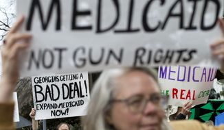 """Chris Bondurant, of Atlanta, rear left, demonstrates during a protest calling for an expansion to Medicaid outside the State Capitol on the first day of the legislative session, Monday, Jan. 13, 2014, in Atlanta. The protest marking the start of the """"Moral Monday"""" movement in Georgia, aims to put pressure on Gov. Nathan Deal to expand Medicaid under the federal health care law. Deal has said the state can't afford the expansion. The effort includes various advocacy groups and the Georgia NAACP, and is modeled after a group in North Carolina. Demonstrators there were arrested weekly last year. (AP Photo/David Goldman)"""