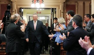 Gov. Terry McAuliffe is greeted with applause as he enters the house chamber to deliver his first speech before the General Assembly at the state Capitol in Richmond, Va., Monday, Jan. 13, 2014. (AP Photo/Richmond Times-Dispatch, Bob Brown)