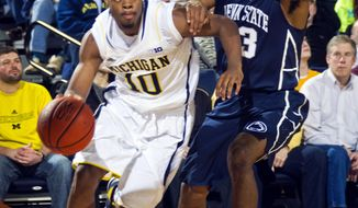 Michigan guard Derrick Walton Jr. (10) dribbles past Penn State guard Geno Thorpe, right, in the first half of an NCAA college basketball game in Ann Arbor, Mich., Tuesday, Jan. 14, 2014. (AP Photo/Tony Ding)