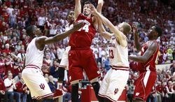 Wisconsin forward Frank Kaminsky rebounds the basketball guarded by Indiana forwards Noah Vonleh, left, and Austin Etherington (13) while Wisconsin forward Nigel Hayes, right, stands near the play in the first half of an NCAA basketball game in Bloomington, Ind., Tuesday, Jan. 14, 2014. (AP Photo/R Brent Smith)