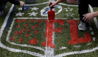 Works paint an NFL logo Tuesday, Jan. 14, 2014, as they prepare CenturyLink Field in Seattle for Sunday's NFL football NFC championship game between the Seattle Seahawks and the San Francisco 49ers. (AP Photo/Ted S. Warren)