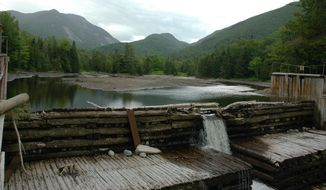 In a June 8, 2012, file photo, water flows over the damaged Marcy Dam in the Adirondack High Peaks in Lake Placid, N.Y. The bridge across Marcy Dam, in a popular hiking region near Lake Placid, has been a favorite photo spot for generations of hikers, but state officials have decided it would be too expensive to rebuild it after it was damaged by Tropical Storm Irene in August 2011.   (AP Photo/Mary Esch, file)