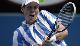 Tomas Berdych of the Czech Republic makes a bachand return to Kenny De Schepper of France during their second round match at the Australian Open tennis championship in Melbourne, Australia, Wednesday, Jan. 15, 2014.(AP Photo/Rick Rycroft)