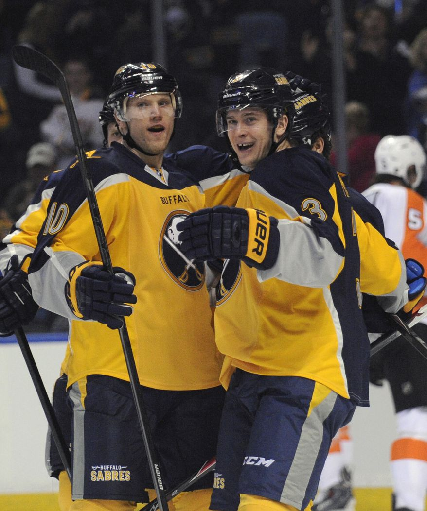 Buffalo Sabres' Christian Ehrhoff (10) celebrates with Mark Pysyk (3) after a goal by Cody Hodgson during the first period of an NHL hockey game against the  Philadelphia Flyers in Buffalo, N.Y., Tuesday, Jan. 14, 2014. (AP Photo/Gary Wiepert)
