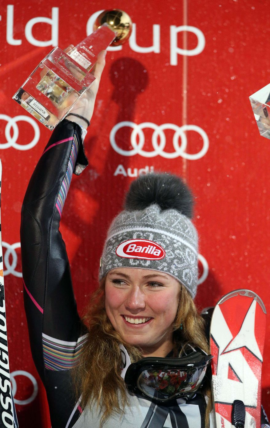 Mikaela Shiffrin, of the United States, celebrates on the podium after winning an alpine ski, women's World Cup slalom in Flachau, Austria, Tuesday, Jan. 14, 2014. American teenager Mikaela Shiffrin held on to a comfortable first-run lead to win a women's World Cup night slalom on Tuesday. (AP Photo/Enrico Schiavi)