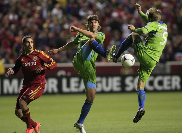 Seattle Sounders defender Jeff Parke, center, teammate defender Adam Johansson (5) clear the ball as Real Salt Lake forward Fabian Espindola (7) looks on in the second half during an MLS Western Conference semifinal soccer match Thursday, Nov. 8, 2012,