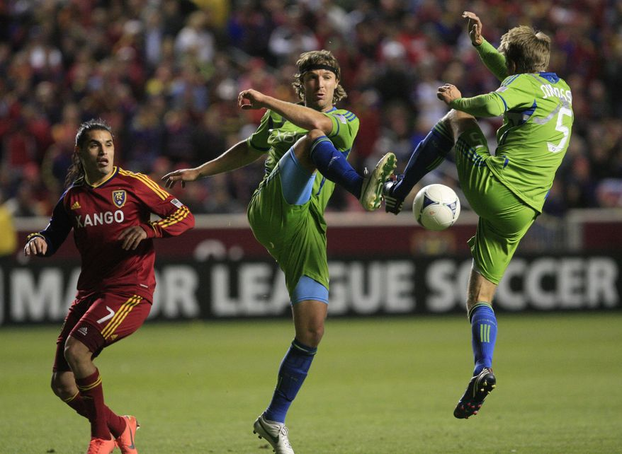 Seattle Sounders defender Jeff Parke, center, teammate defender Adam Johansson (5) clear the ball as Real Salt Lake forward Fabian Espindola (7) looks on in the second half during an MLS Western Conference semifinal soccer match Thursday, Nov. 8, 2012, in Sandy, Utah. The Sounders defeated Real Salt Lake. The match, the second of a two-match aggregate game, ended with a score of  1-0. (AP Photo/Rick Bowmer)