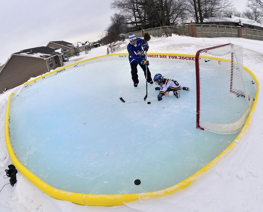 In this Jan. 7, 2014 photo, Andy Seaton and his 7-year old son Augie take in a cold afternoon of hockey practice on the family's backyard 25-foot-by-40-foot ice rink in Germantown Hills, Ill. (AP Photo/Journal Star, Ron Johnson)