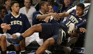 Pittsburgh's Chris Jones (12) crashes into the Georgia Tech bench as he chases a loose ball in the first half of an NCAA college basketball game Tuesday, Jan. 14, 2014, in Atlanta. (AP Photo/John Bazemore)