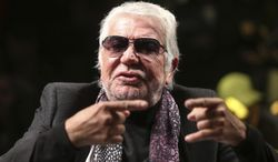 Italian fashion designer Roberto Cavalli gestures as he talks with journalists prior to the start of the Roberto Cavalli men's Fall-Winter 2014 show, part of the Milan Fashion Week, unveiled in Milan, Italy, Tuesday, Jan.14, 2014. (AP Photo/Luca Bruno)