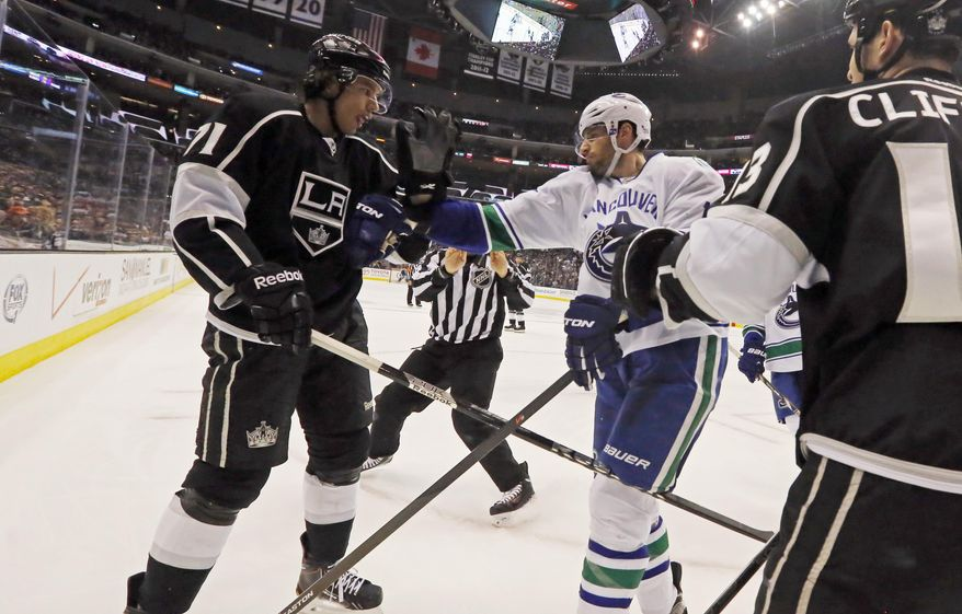 Vancouver Canucks center Ryan Kesler (17), right, and Los Angeles Kings center Jordan Nolan (71) square off in the second period of an NHL hockey game in Los Angeles Monday, Jan. 13, 2014.  (AP Photo/Reed Saxon)
