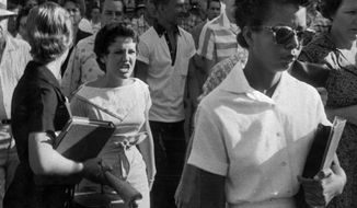 FILE - In this Sept. 4, 1957 file photo, students of Central High School in Little Rock, including Hazel Bryan, shout insults at Elizabeth Eckford as she calmly marches down to a line of National Guardsmen, who blocked the main entrance and would not let her enter. Five decades and $1 billion after an infamous racial episode made Little Rock a symbol of school segregation, the legal fight to ensure all of its children receive equal access to education has ended. (AP Photo/Arkansas Democrat Gazette/Will Counts, File)