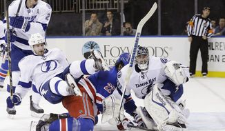 Tampa Bay Lightning's Tom Pyatt (11) pushes New York Rangers' Brian Boyle (22) into goalie Ben Bishop (30) during the second period of an NHL hockey game, Tuesday, Jan. 14, 2014, in New York. (AP Photo/Frank Franklin II)