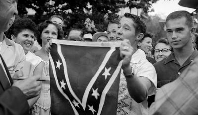 FILE - In this Sept. 3, 1957 file photo, Paul Davis Taylor displays a Confederate flag in front of Little Rock Central High School in Little Rock, Ark. Taylor was among some 500 people who gathered across the street from the school, which had been scheduled to integrate. Five decades and $1 billion after an infamous racial episode made Little Rock a symbol of school segregation, the legal fight to ensure all of its children receive equal access to education has ended. (AP Photo/File)