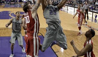Kansas State's Wesley Iwundu (25) gets past Oklahoma's Ryan Spangler (00) to put up a shot during the second half of an NCAA college basketball game Tuesday, Jan. 14, 2014, in Manhattan, Kan. Kansas State won 72-66. (AP Photo/Charlie Riedel)
