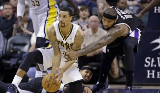 Indiana Pacers guard George Hill, left, tries to makes a pass after picking up a loose ball in front of Sacramento Kings guard Isaiah Thomas, center, as center DeMarcus Cousins reaches for the ball in the first half of an NBA basketball game in Indianapolis, Tuesday, Jan. 14, 2014.  (AP Photo/Michael Conroy)