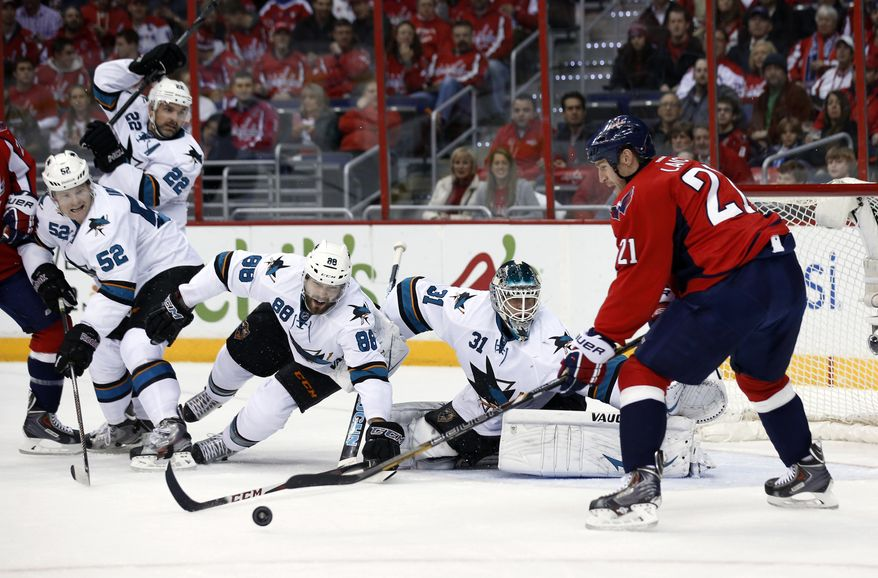 San Jose Sharks defenseman Matt Irwin (52), defenseman Dan Boyle (22), right wing Brent Burns (88) and goalie Antti Niemi (31), from Finland, defend on a shot by Washington Capitals center Brooks Laich during the first period of an NHL hockey game, Tuesday, Jan. 14, 2014, in Washington. (AP Photo/Alex Brandon)
