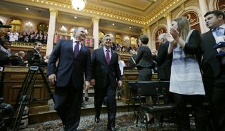 Iowa Gov. Terry Branstad, center, is escorted into the Iowa House chambers before  delivering his Condition of the State address before a joint session of the Iowa Legislature, Tuesday, Jan. 14, 2014, at the Statehouse in Des Moines, Iowa.(AP Photo/Charlie Neibergall)
