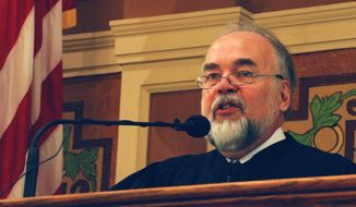 South Dakota Supreme Court Chief Justice David Gilbertson gives his annual State of the Judiciary speech to a joint session of the South Dakota Legislature on Wednesday, Jan. 15, 2014, in Pierre, S.D. Gilbertson says the court system is doing its part to overhaul South Daktoa's criminal justice system. (AP Photo/Chet Brokaw)