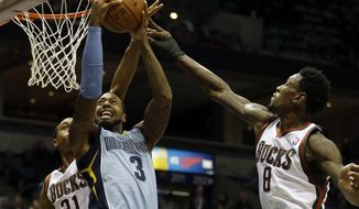 Memphis Grizzlies' James Johnson (3) goes up to shoot against Milwaukee Bucks' John Henson (31) and Larry Sanders (8) during the first half of an NBA basketball game on Wednesday, Jan. 15, 2014, in Milwaukee. (AP Photo/Morry Gash)