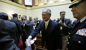 Rhode Island Gov. Lincoln Chafee, center, greets people on the floor of the House Chamber before delivering his State of the State address at the Statehouse, Wednesday, Jan. 15, 2014 in Providence. The annual speech traditionally sets out a governor's priorities for the year. It is Chafee's fourth and final such address. (AP Photo/Steven Senne)