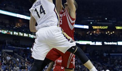 New Orleans Pelicans center Jason Smith (14) blocks an attempted slam dunk by Houston Rockets small forward Chandler Parsons in the first half of an NBA basketball game in New Orleans, Wednesday, Jan. 15, 2014. (AP Photo/Gerald Herbert)