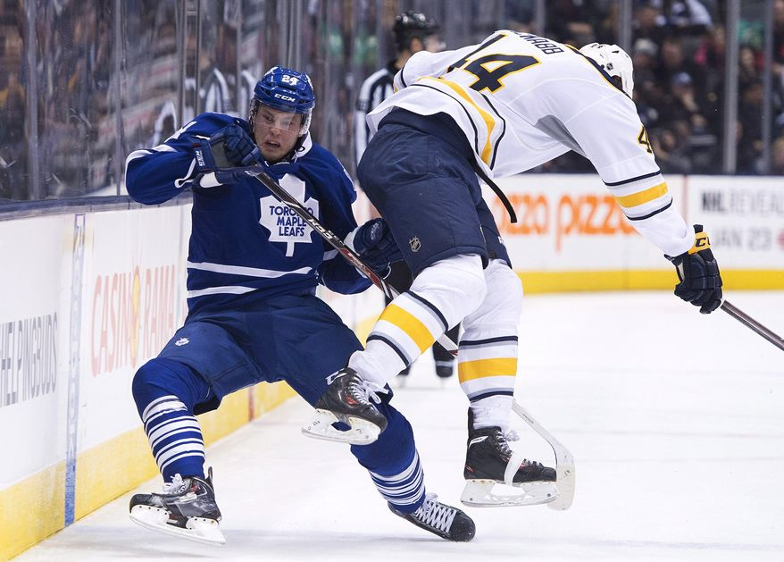 Toronto Maple Leafs forward Peter Holland, left, gets taken out by Buffalo Sabres defenseman Brayden McNabb, right, during the second period of an NHL hockey game, Wednesday, Jan. 15, 2014 in Toronto. (AP Photo/The Canadian Press, Nathan Denette)