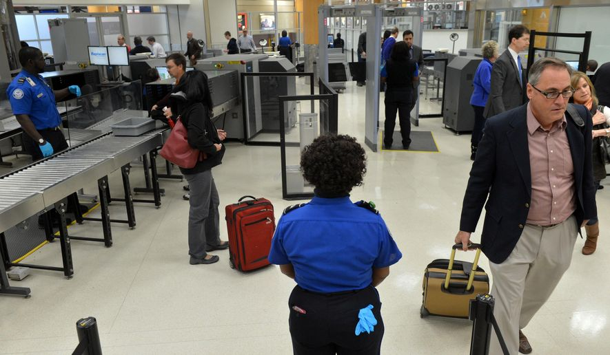 TSA agents man the checkpoint for pre-cleared passengers at Hartsfield-Jackson Atlanta International Airport on Wednesday, Jan. 15, 2014 in Atlanta. (AP Photo/Atlanta Journal-Constitution, Kent D. Johnson) ** FILE **