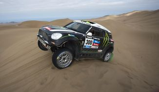 Stephane Peterhansel and co-pilot Jean Paul Cottret, both of France, drive their Mini through the dunes during the tenth stage of the Dakar Rally between the cities of Iquique and Antofagasta, Chile, Wednesday, Jan. 15, 2014. (AP Photo/Victor R. Caivano)
