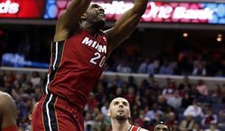 Miami Heat center Greg Oden (20) dunks the ball in front of Washington Wizards center Marcin Gortat (4), from Poland, in the first half of an NBA basketball game on Wednesday, Jan. 15, 2014, in Washington. It was Oden's first NBA regular-season game in more than four years. (AP Photo/Alex Brandon)