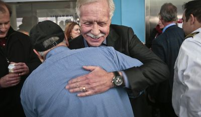 "Captain Chesley ""Sully"" Sullenberger III, center, pilot of U.S. Airways Flight 1549, hugs Louis Salerno, a senior deck hand with N.Y. Water ways ferry, on Wednesday, Jan. 15, 2014 in New York.  Salerno rescued Sullenberger after the Captain safely glided Flight 1549 with 155 passengers and crew to a water landing.  Sullenberger gathered with some survivors and rescuers to mark the fifth anniversary of the event known as the ""miracle on the Hudson."" (AP Photo/Bebeto Matthews)"
