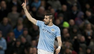 Manchester City's Alvaro Negredo celebrates after scoring his second goal against Blackburn during their English FA Cup third round replay soccer match at The City of Manchester Stadium, Manchester, England, Wednesday, Jan. 15, 2014. (AP Photo/Jon Super)
