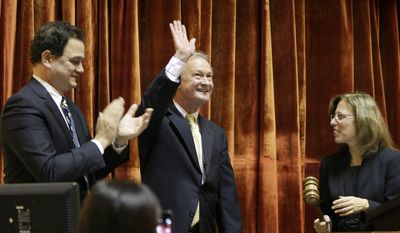 Rhode Island Gov. Lincoln Chafee, center, waves before delivering his State of the State address as Speaker of the House Gordon Fox, left, and Senate President Teresa Paiva Weed, right, applaud and look on in the House chambers of the Statehouse, Wednesday, Jan. 15, 2014 in Providence, R.I. The annual speech traditionally sets out a governor's priorities for the year. (AP Photo/Steven Senne)