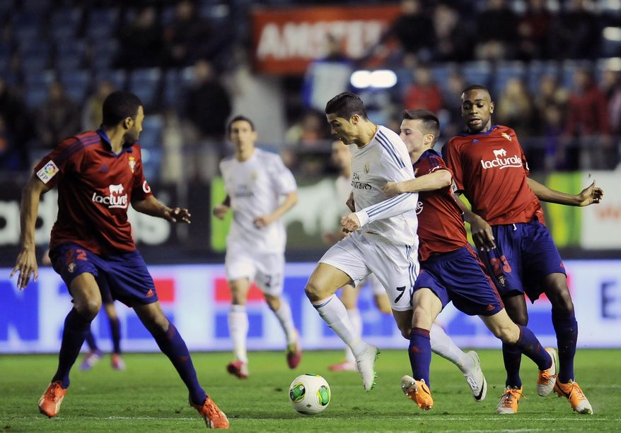 Real Madrid's Cristiano Ronaldo of Portugal, center, duels for the ball with Osasuna's Oier Sanjurjo, second right, during their Spanish Copa del Rey round-16 second leg soccer match at El Sadar stadium, in Pamplona, northern Spain, Wednesday, Jan. 15, 2014. (AP Photo/Alvaro Barrientos)