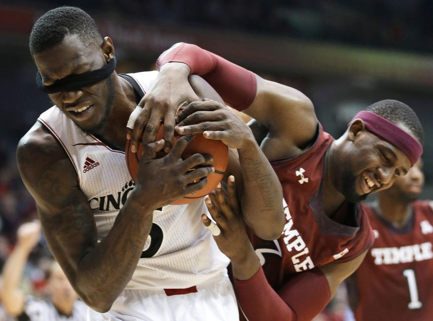 Cincinnati forward Justin Jackson, left, has his head band pulled over his eyes while fighting for a rebound against Temple forward Anthony Lee during the second half of an NCAA college basketball game, Tuesday, Jan. 14, 2014, in Cincinnati. Cincinnati won 69-58. (AP Photo/Al Behrman)