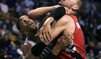 Boston Celtics forward Jared Sullinger, left, tangles with Toronto Raptors center Jonas Valanciunas on a rebound during the first quarter of an NBA basketball game in Boston, Wednesday, Jan. 15, 2014. (AP Photo/Charles Krupa)