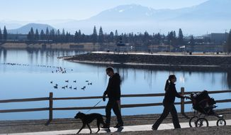Joggers and dog-walkers make their way around the Sparks Marina, Wednesday Jan. 15, 2014  in Sparks, Nev. State wildlife biologists are trying to figure out what caused the kill-off the man-made lake's entire stocked fishery  an estimated 100,000 trout, bass and catfish. The 77-acre marina sits in an old rock quarry along U.S. Interstate 80 just east of Reno. (AP Photo/Scott Sonner).