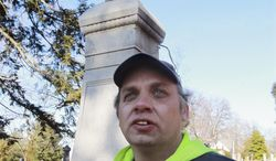 ADVANCE FOR USE SUNDAY, JAN. 19 AND THEREAFTER - In this Dec. 24, 2014 photo, Woodlawn Cemetery sexton Edward Ricks poses in front of an ornate grave marker at the Edwardsville, Ill., cemetery that is still recovering from a summer storm. The statue on the top had been knocked off in the storm. (AP Photo/Belleville News-Democrat, Tim Vizer)