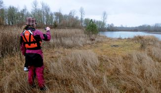 In this Jan. 9, 2014 photo, Kate Ross, outreach and education coordinator for Willamette Riverkeeper, photographs a clearing with a view of the river near Monroe, Ore. that could be a place for a future campsite when Norwood Island is purchased. (AP Photo/The Corvallis Gazette-Times, Amanda Cowan)