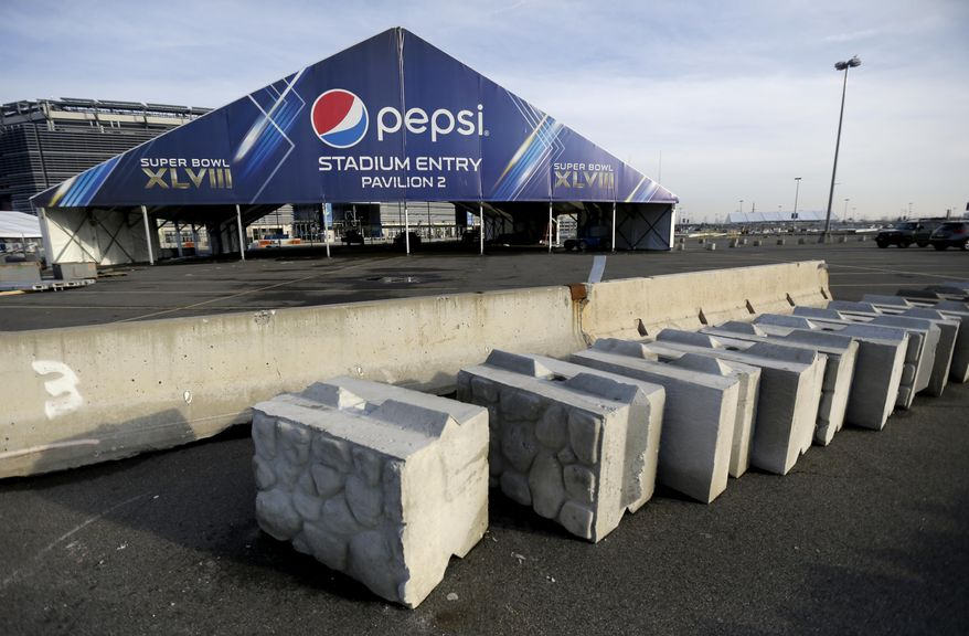This photo shows concrete barricades in the parking lot of MetLife Stadium as crews prepare the grounds ahead of Super Bowl XLVIII, Wednesday, Jan. 15, 2014, in East Rutherford, N.J. Police officials say security for the Super Bowl will include about 4,000 government and private officers assigned to the stadium on game day. Fans arriving at the game by mass transit on Feb. 2 will encounter a security perimeter extending 300 feet from entrances to the stadium. They'll be funneled into temporary pavilions for airport-style screening. (AP Photo/Julio Cortez)